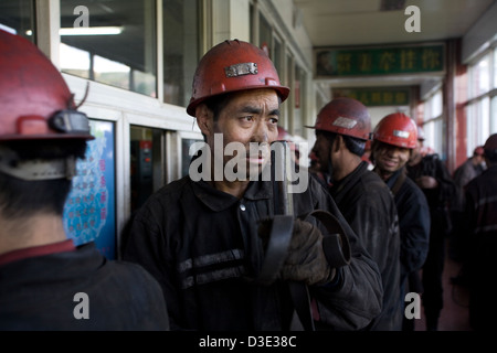 XIMING COAL MINE, TAIYUAN, CHINA - AUGUST 2007: Miners at the end of their shift hand in their miners' lamps for - Stock Photo