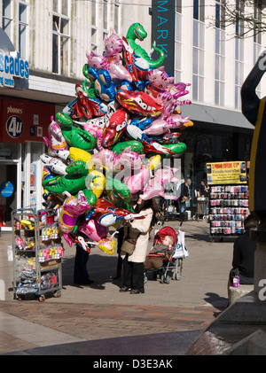 woman selling balloons in city center on a sunny day - Stock Photo