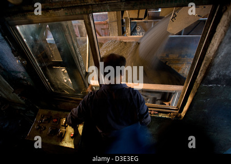 XIMING COAL MINE, TAIYUAN, CHINA - AUGUST 2007: The coal loading operator runs coal into empty rail trucks for delivery - Stock Photo