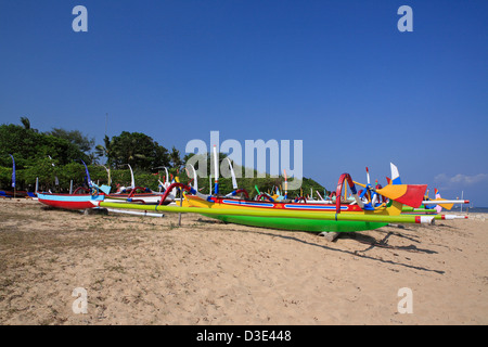Brightly colored fishing boats, called Jukungs, lined up on Sanur Beach, Bali, Indonesia - Stock Photo
