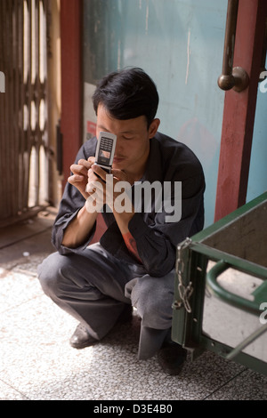 PU LIAN TA COAL MINE, ORDOS, INNER MONGOLIA, CHINA - AUGUST 2007:  An off-duty miner sends a text message on his - Stock Photo