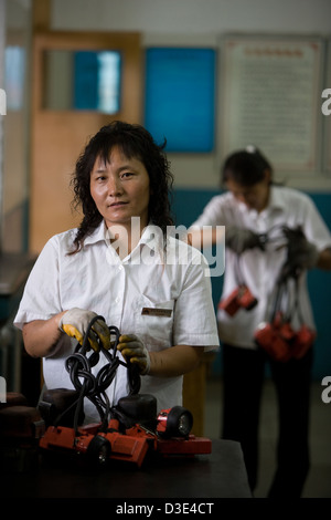 PU LIAN TA COAL MINE, ORDOS, INNER MONGOLIA, CHINA - AUGUST 2007: Women workers sort lamps and battery packs returned - Stock Photo