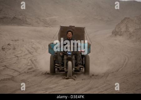 WUDA COAL FIELD, WU HAI, INNER MONGOLIA, CHINA - AUGUST 2007: Jin Cheng Gui, 20, drives his three wheeled pick-up - Stock Photo