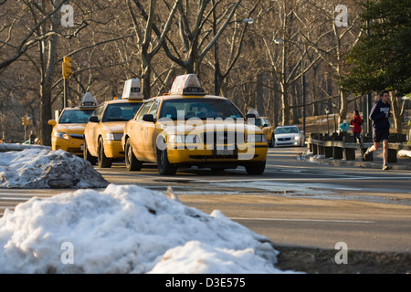 Yellow New York City Taxicabs lined up and sharing the road with joggers on the East Drive in New York City's Central - Stock Photo