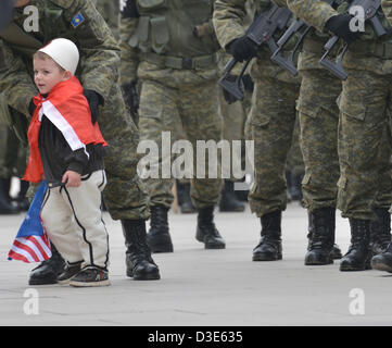 Child wearing traditional hat runs onto the street during Independence Day military parade, Pristina, Kosovo, on - Stock Photo