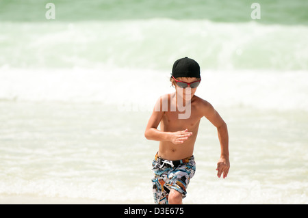 Young boy running through the ocean water on a beach wearing sunglasses and backwards hat. - Stock Photo