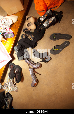 A variety of formal and informal teen shoes left behind at a dance party. - Stock Photo