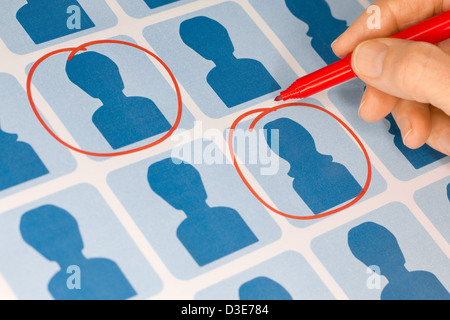 Hand Selecting Candidates with Red Pen - Stock Photo