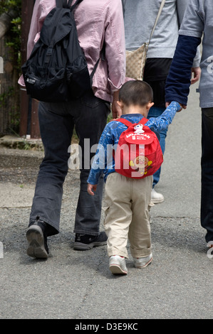 A little Japanese boy wearing an Anpanman backpack walks hand in hand with one of his parents. - Stock Photo