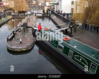A narrowboat negotiates Camden Lock on the Regent's Canal, through Camden Town in London. - Stock Photo