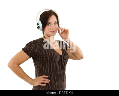 Young confident woman listening in headphones with microphone - Stock Photo