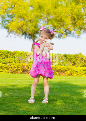Photo of cute little girl holding in hands soft toy, sweet baby playing outdoors, adorable small female having fun - Stock Photo