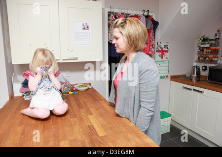 Toddler having a temper tantrum in the kitchen with mum. - Stock Photo