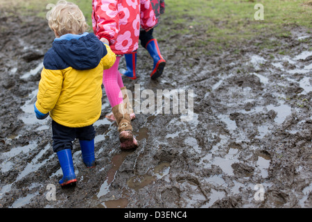 Children walking through Muddy Puddles - Stock Photo