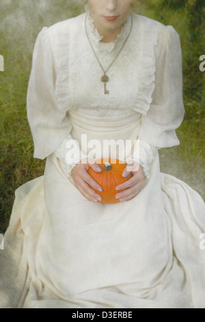a woman in a victorian dress is sitting on grass and holding a pumpkin on her lap - Stock Photo