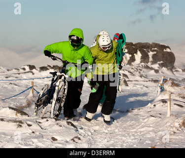 mountain biker carries and pushes bike through snow at the top of Nevis range Scottish Highlands with snowboarder - Stock Photo