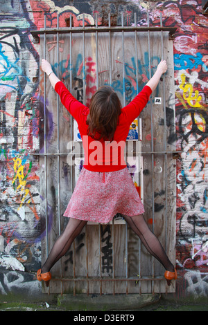 Female in front of colourful wall,Brick Lane, East London E1 - Stock Photo