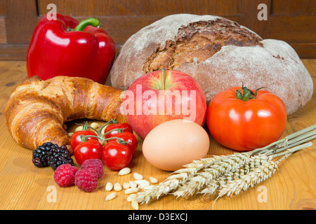 Different types of food such as bread, a tomato, apple, pine seeds, raspberry and a pretzel - Stock Photo