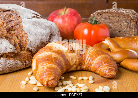 Different types of food such as bread, a tomato, apple, pine seeds and a pretzel - Stock Photo