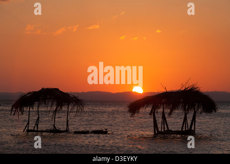 Sunset silhouettes the washing platforms in Moyogalpa on Isla de Ometepe on Lake Nicaragua in Nicaragua - Stock Photo