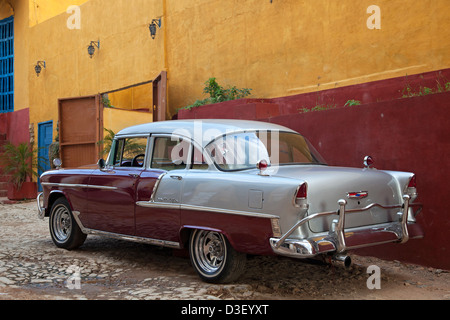 Pastel coloured house and old 1950s vintage American Chevrolet Bel Air car / Yank tank in Trinidad, Cuba, Caribbean - Stock Photo