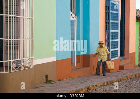 Old Cuban man walking along pastel coloured houses with barrotes and grilles in Trinidad, Cuba - Stock Photo