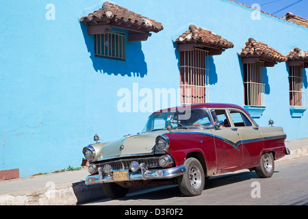 Pastel coloured house and old 1950s vintage American car / Yank tank in Trinidad, Cuba, Caribbean - Stock Photo