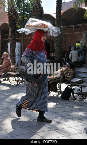 Moroccan woman carrying moroccan bread rolls on her head walking through plaza  to one of the many food vendor market - Stock Photo