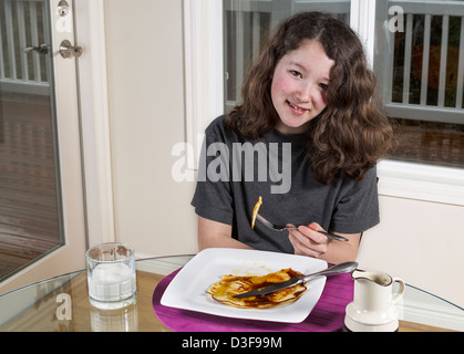 Young teen girl eating her breakfast consisting of pancakes, maple syrup and milk while sitting at the dinning room - Stock Photo