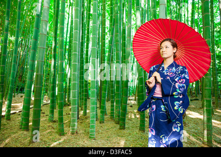 Japanese woman wearing kimono and holding red parasol stands in bamboo grove - Stock Photo