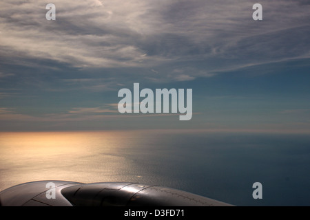 From the window of an airplane passing contemplate infinity of a blue to a soft orange, the colors of a sunset in - Stock Photo