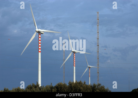 Porto Torres, Italy, electricity pylons and wind wheels of the power utility Enel SpA - Stock Photo