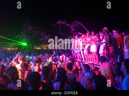 Young people at a Full Moon Party girl holding a small ...