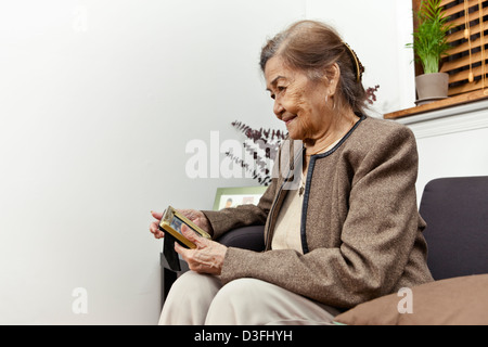 A female senior citizen of 80 plus years is holding framed photo of loved one. - Stock Photo