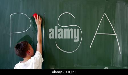 (dpa) - A boy is wiping a blackboard on which the acronym PISA (programme for international student assessment) - Stock Photo