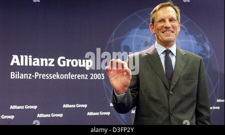 (dpa) - Michael Diekmann, new CEO of the Allianz AG, the financial services and insurance provider, stands in front of the company logo and smiles during a press conference in Munich, Germany, 20 March 2003. Diekmann continues the company policy of providing integrated financial services by holding on to the lossy Dresdner Bank. The Allianz AG wants to raise new capital in billions