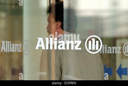 (dpa) - An employee of Allianz AG, the financial services and insurance provider, stands behind a glass revolving door with the company logo on it at the company's headquarters in Munich, Germany 20 March 2003. Michael Diekmann, new CEO of the Allianz AG, said during a press conference that the company should continue its policy of providing integrated financial services by holding