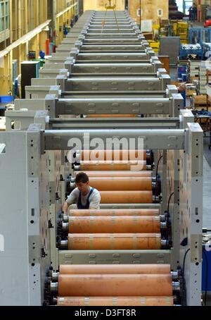 (dpa) - An employee of the manufacturer of printing machines MAN Roland works on printing units in a factory in - Stock Photo