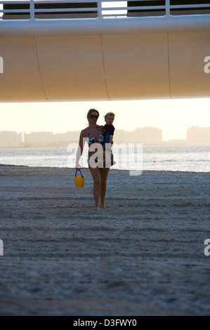 Woman and infant walk along on the beach beneath the access roadway to the Burj Al Arab seven star hotel in Dubai - Stock Photo