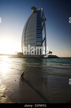 Small boy plays on the beach at sunset in front of the 7 star Burj Al Arab hotel in Dubai UAE. This is the only - Stock Photo