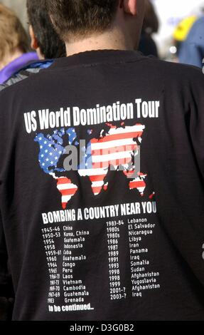 (dpa) - An objector wears a T-shirt which reads 'US World Domination Tour, bombarding a country near you' during - Stock Photo