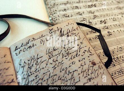 (dpa files) - A copy of Johann Sebastian Bach's Orchestral Suite in D Major BWV 1069 (back) and a handwritten entry - Stock Photo