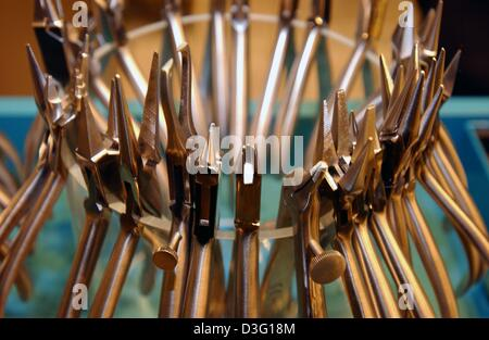 (dpa) - A collection of dental forceps hang around the edge of a glass at the 'IDS', the international trade fair - Stock Photo