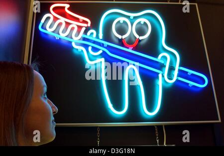 (dpa) - Katharina looks at a neon lit sign of a tooth holding a toothbrush at the 'IDS', the international trade - Stock Photo