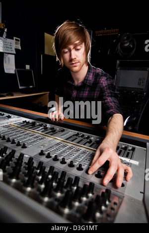 Sound engineer using a studio mixing desk. Selective focus on Sound desk. - Stock Photo
