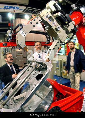 (dpa) - Visitors look at a spot welding robot of the company Reis Robotics Obernburg at the Intec industry trade - Stock Photo
