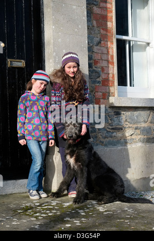 Girls with Irish Wolfhound outside a rural Cottage in Ireland - Stock Photo