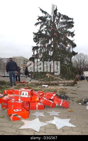 (dpa) - A banner reading 'Gekuerzt' (slashed/shortened) is fixed at the tip of a slashed Christmas tree in front - Stock Photo