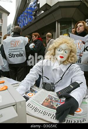 (dpa) - A group of journalists, wearing plastic waistcoats which read 'journalists on strike', and a symbolic doll - Stock Photo