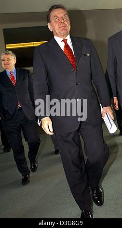 (dpa) - German Chancellor Gerhard Schroeder (R) and Joschka Fischer (background), German Foreign Minister and Vice Chancellor, arrive at a press conference in Berlin, 19 October 2003. The leading politicians of the red-green coalition held a meeting in Berlin to discuss the future of the pensions fund. Announcing a five-point plan for overhauling Germany's crumbling pension benefit